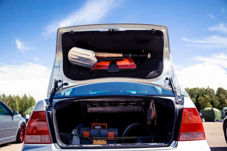 Photo pour Open the trunk of a silver car that stands on the street. In the trunk of a shovel, baseball bat and warning triangle. - image libre de droit