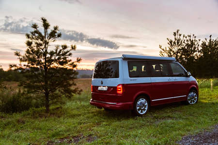 Photo for St. Petersburg, Russia - July 22, 2019: Red and white colored modern Volkswagen Multivan California Ocean (Transporter). Is Parked in the forest at sunrise. Back side view - Royalty Free Image