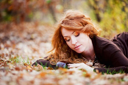 The red-haired girl in autumn leaves 