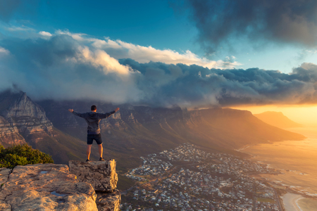 Foto de Young man standing on the edge at the top of Lion's head mountain in Cape Town with a beautiful sunset view - Imagen libre de derechos