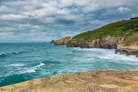 Photo pour High sandy cliffs and waves of Pacific ocean at Tunnel beach, New Zealand - image libre de droit