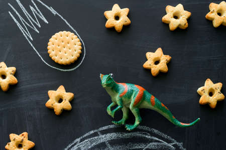 Photo pour plastic dinosaur and cookies on the chalkboard, play and learning with the children,  dinosaurs became extinct because of a meteorite concept - image libre de droit
