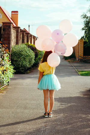Photo for little girl in a yellow t-shirt and a blue tutu skirt holds a bunch of balloons and walks down the street with her back to the camera - Royalty Free Image