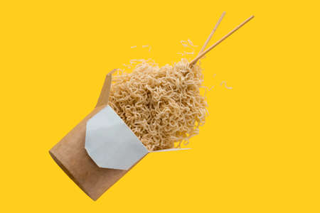 Photo for instant noodles with chopsticks  flying on yellow background, asian fast food - Royalty Free Image