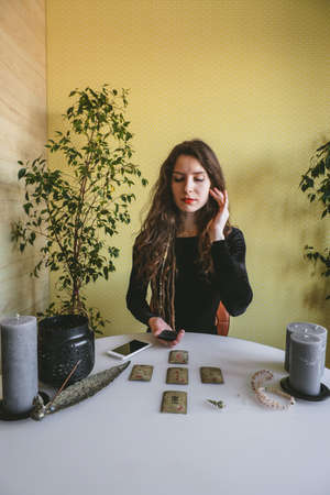 Photo pour beautiful young woman in a black corduroy dress is guessing on cards with runes - image libre de droit
