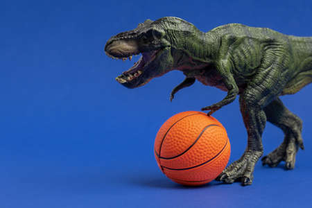 Foto per Green dinosaur toy with basketball ball. Basketball minimal card blue background. - Immagine Royalty Free