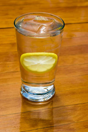 A glass of ice water with a slice of lemon, sitting on a wooden table.