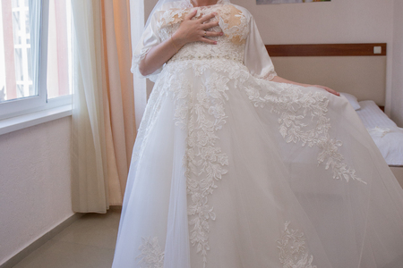Foto de bride in dressing gown and wedding dress in hands - Imagen libre de derechos