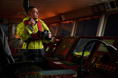 Photo for Navigator. pilot, captain as part of ship crew performing daily duties with VHF radio, binoculars, logbook, standing nearby to ECDIS and radar station on board of modern ship with high quality navigation equipment on the bridge. Great design for navigation, safety of shipping, cargo carriage puproses. - Royalty Free Image