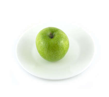 Ripe green ripe apple lays on plate isolated on white
