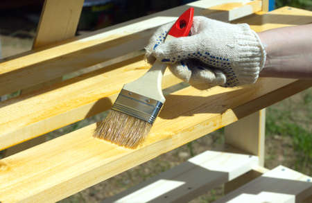 Female hand in textile glove paint wooden shelving outdoors closeup