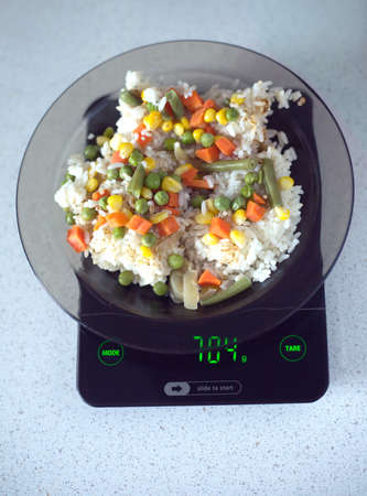 Translucent white plate with rice and vegetables is at home kitchen electronics scales to count calories in food. Top view photo closeupの写真素材