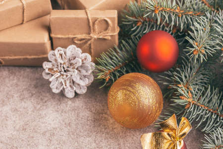 Craft gift boxes and Christmas decoration - Christmas tree branches and cones on slate marble background. Horizontal view. Copy space.