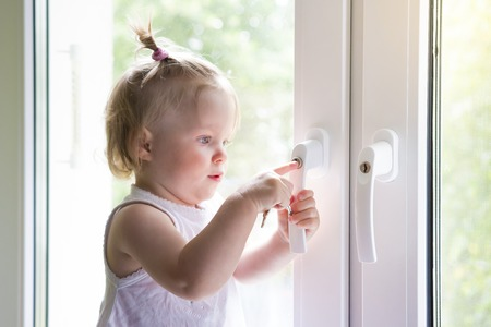 Child opens window with lock. Protection from falling out of child from window. little girl is standing on windowsill. child plays with keys at the window