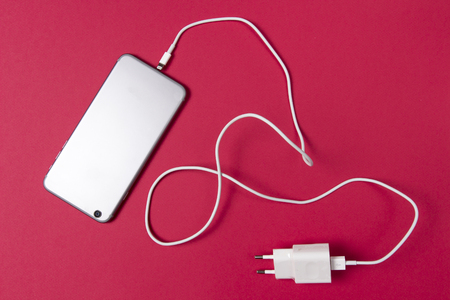 Photo pour modern smartphone and connected charger cable on pink background - image libre de droit