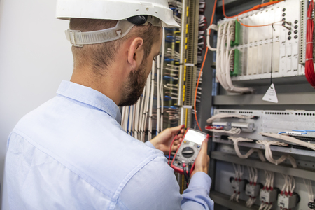 Foto de Young adult electrician builder engineer inspecting electric equipment in distribution fuse box. Electrical engineer worker in control panel. Maintenance electro box with multimeter. - Imagen libre de derechos