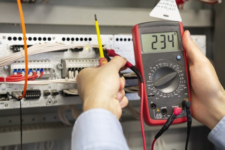 Photo pour Electrician measurements with multimeter tester. Male Technician Examining Fusebox With Multimeter Probe. Closeup of multimeter in hands of engineer - image libre de droit