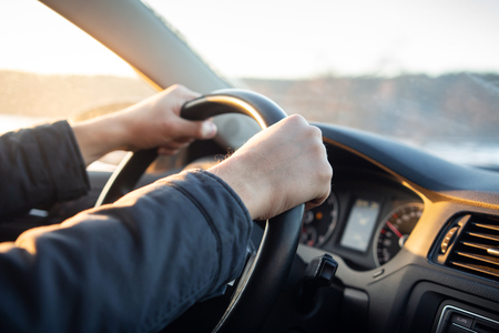 Photo pour Close-up of driver's hand on steering wheel of car in cabin - image libre de droit