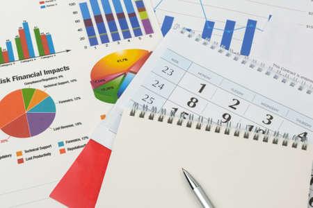 Foto de Business goal concept. Business accessory, graph charts, calendar, notebook and pen on the table - Imagen libre de derechos