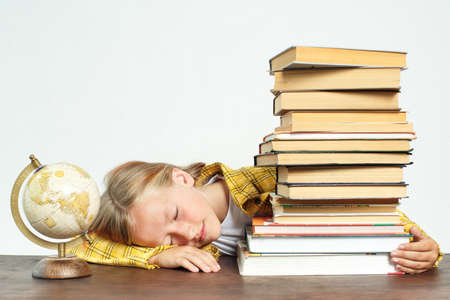 Photo pour Education concept. The student fell asleep while doing her homework. Near books and a globe - image libre de droit