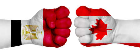 Photo for The concept of the struggle of peoples. Two hands are clenched into fists and are located opposite each other. Hands painted in the colors of the flags of the countries. Canada vs Egypt - Royalty Free Image