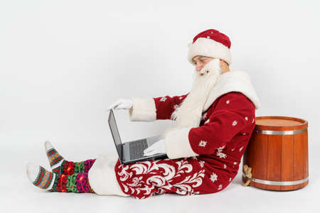 Photo pour Christmas and New Years concept. Santa Claus is sitting on the floor and working at a laptop. Isolated background. - image libre de droit