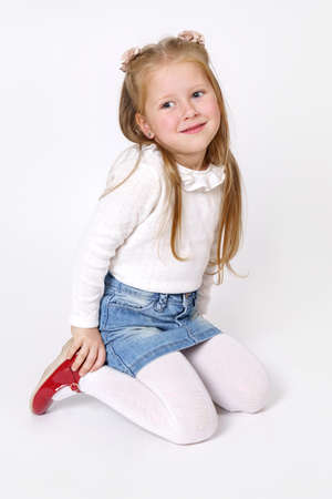 Photo for Children concept. The girl is sitting on the floor. Isolated over white background. - Royalty Free Image