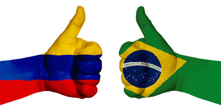 Photo for Politics and finance concept. Two hands with a raised finger. They portray the gesture class, managed to negotiate. On the hands of the image of the flags of the countries, Brazil and Colombia - Royalty Free Image