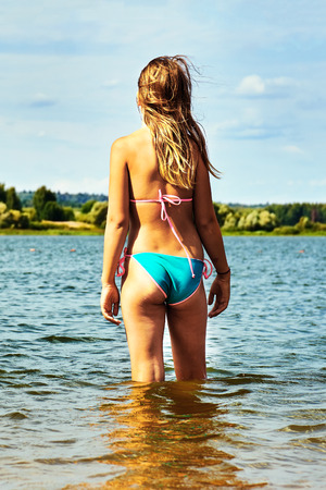 Photo pour Teenager girl wearing bikini stands in the water of a beautiful lake and enjoys warm weather at summer vacations - image libre de droit