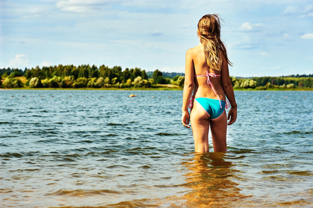 Foto de Teenager girl wearing bikini stands in the water of a beautiful lake and enjoys warm weather at summer vacations - Imagen libre de derechos