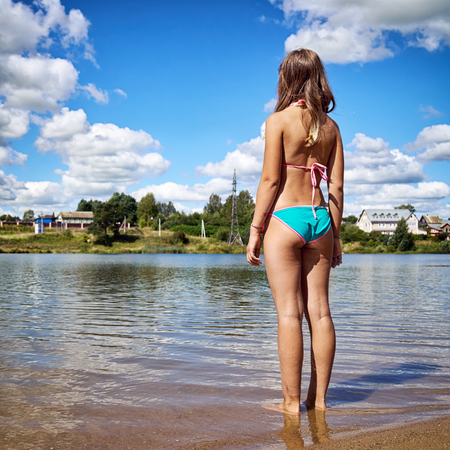 Photo pour Teenager girl wearing bikini stands in the water of russian suburban lake and enjoys warm weather and is going to swim at summer vacations. Summer bathing in a country lake or pond in Russia. - image libre de droit