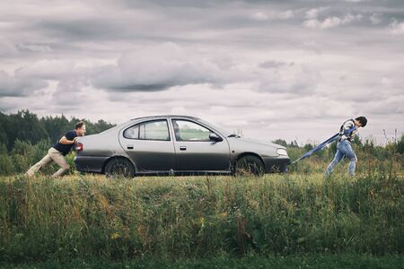 Foto de Man and a woman pushing their broken car down the country road. Middle-aged couple trying to bring the car to the car service station in summer cloudy day during journey - Imagen libre de derechos