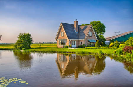 Photo pour Red bricks house in countryside near the lake with mirror reflection in water, Amsterdam, Holland, Netherlands, HDR - image libre de droit