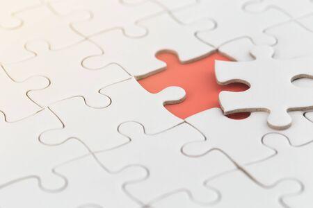 Photo pour white jigsaw puzzle with missing piece with orange color. - image libre de droit