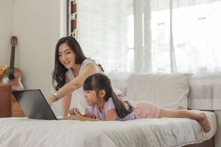 Photo for Mother and daughter using laptop on bed in holiday at home. - Royalty Free Image
