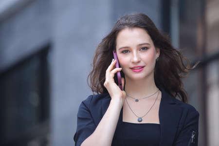 Photo pour businesswoman calling on the mobile phone walk on city street. - image libre de droit