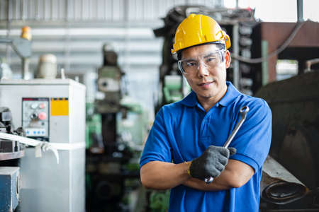 Photo pour portrait image asian engineer men wearing uniform safety and holding wrench tool in factory.  male professional maintenance repair machine at industrial. - image libre de droit