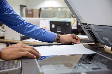 Foto de Businessmen load paper in the copier and useing photocopier for scanning or useing printer for printout exrox documents papers at office. - Imagen libre de derechos