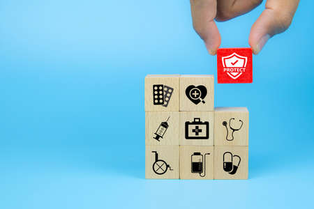 Photo pour Hand choose medical icon on cube wooden toy blocks stack in with other medical symbols concepts of illness treatment and health safety insurance. - image libre de droit