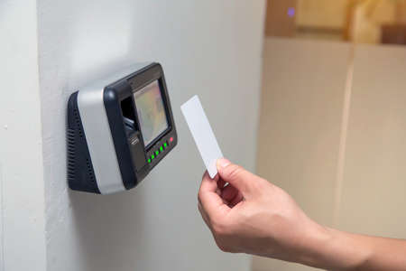 Photo for Office man using the ID card to scan at the access control system machine for check attendance and open the security door - Royalty Free Image