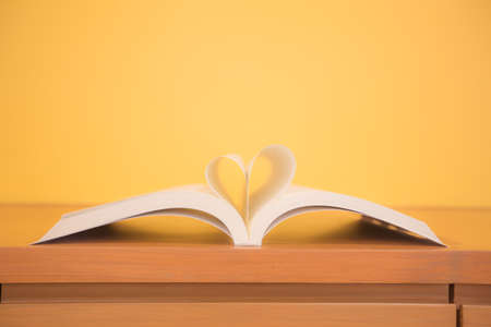 Photo pour Close up page of a book in heart shape on the table at library room of lifestyle love to read and reading a text book and February valentine day concepts. - image libre de droit