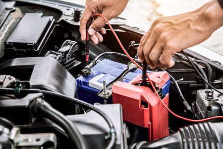 Photo pour Close up hand of auto mechanic are using measuring equipment tool for checking car battery. Concepts of car fix repair and service maintenance. - image libre de droit
