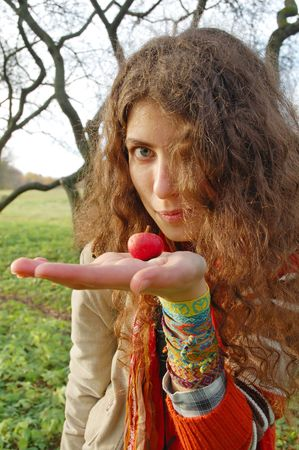 Woman holding a small red apple in hand