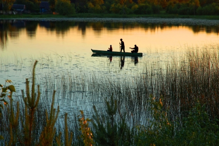 Photo pour Silhouette of three fishermen in a small boat on a lake at sunset - image libre de droit