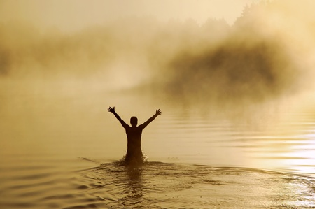 Silhouette of a male with raised arms in the water