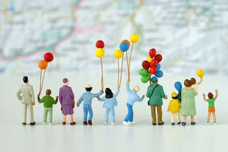 Miniature people with family holding balloon looking at map in the background as happy family travel concept.