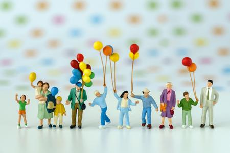 Foto de Miniature people with family holding balloon with pop color dot background as happy family concept. - Imagen libre de derechos