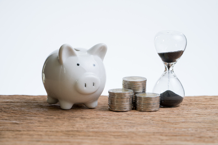 Photo pour Finance or investment time with hourglass or sandglass, piggy bank and stack of coins on wooden table with white background. - image libre de droit