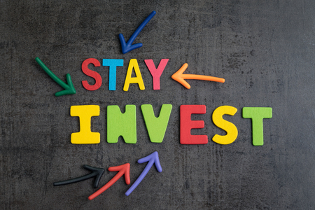 Stay invested in stock with no market timing concept, arrows pointing to words STAY INVEST on loft cement wall.