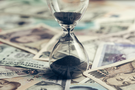 Foto de Time running or long term investment concept with sand glass or hour glass on many countries international banknotes, US Dollar, Thai Baht, Yuan, japan yen in vintage tone. - Imagen libre de derechos